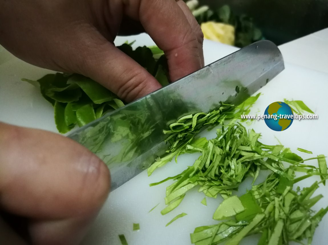 Slicing the kaffir lime leaves for Perut Ikan