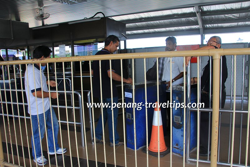 Passenger paying the fare for boarding the Penang Ferry