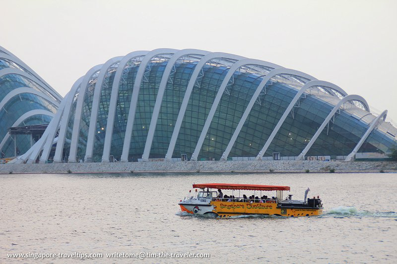 A Singapore Ducktour amphibious craft cruising down Marina Channel past the Conservatory Complex of the Gardens by the Bay