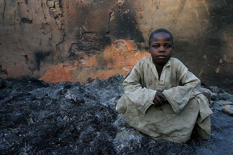 Boy with remains of house burnt in 2007 civil war, in Birao, CAR
