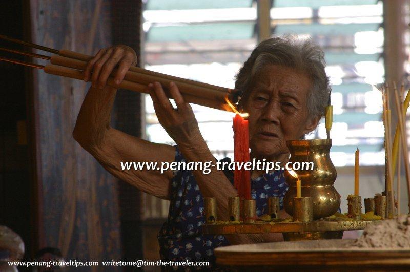 A devotee lighting joss sticks in Kuan Yin See